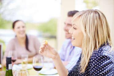 Smiling woman having dinner with friends - ZEF001477
