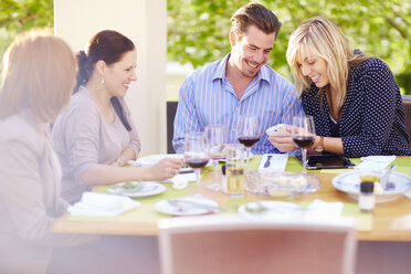 Woman showing cell phone to friends at dining table - ZEF001482