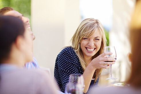 Happy friends with red wine glasses outdoors - ZEF001484