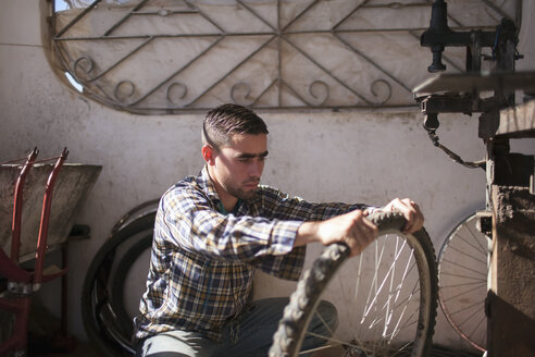 Cuba, Matanzas, Jaguey Grande, young man working at bicycle repair shop - NN000082