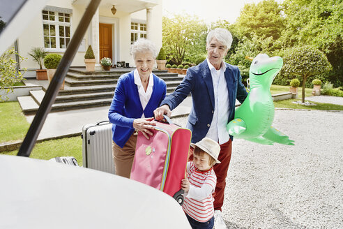Grandparents with granddaughter and luggage on driveway - RORF000114