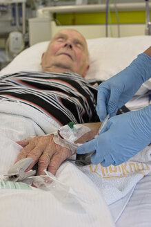 Taking of a blood sample from senior man being in intensive care after heart attack - LAF001086