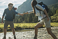 Austria, Tyrol, Tannheimer Tal, two young  hikers crossing water - UUF002098
