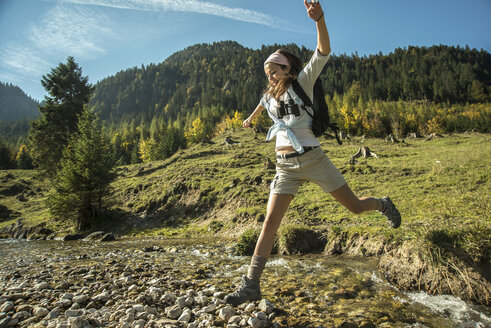 Austria, Tyrol, Tannheimer Tal, young female hiker crossing water - UUF002126