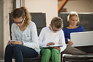 Mother and her two children relaxing with digital tablet, smartphone and laptop on the terrace - PAF001007