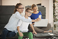Mother and her two children relaxing with digital tablet, smartphone and laptop on the terrace - PAF001012