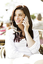 Portrait of happy young woman telephoning with smartphone at a pavement cafe - GDF000468