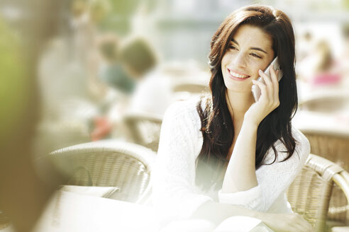 Smiling young woman telephoning with smartphone at a pavement cafe - GDF000470