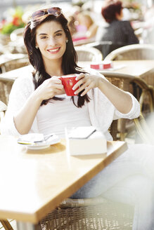 Happy young woman relaxing at a pavement cafe - GDF000474