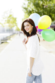 Portrait of happy young woman with a bunch of balloons - GDF000481