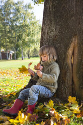 Little girl leaning at tree trunk looking at bunch of autumn leaves in her hands - LVF002004