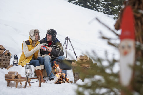 Smiling couple in snow at camp fire - HHF004950
