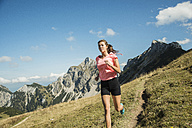 Austria, Tyrol, Tannheim Valley, young woman jogging in mountains - UUF002053