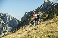 Austria, Tyrol, Tannheim Valley, young couple jogging in mountains - UUF002060