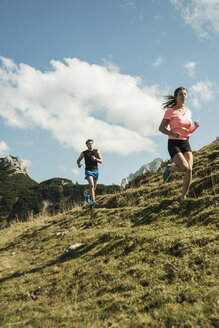 Austria, Tyrol, Tannheim Valley, young couple jogging in mountains - UUF002065