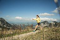 Austria, Tyrol, Tannheim Valley, young woman nordic walking in mountains - UUF002080