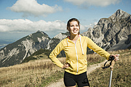 Austria, Tyrol, Tannheim Valley, smiling young woman holding nordic walking sticks in mountains - UUF002085