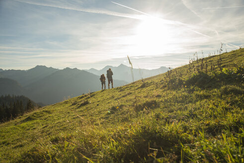 Austria, Tyrol, Tannheimer Tal, young couple hiking on alpine meadow - UUF002229