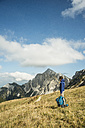 Austria, Tyrol, Tannheimer Tal, hiker with backpack on alpine meadow - UUF002236