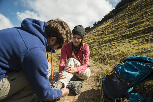 Austria, Tyrol, Tannheimer Tal, young man caring for injured woman on hiking tour - UUF002243