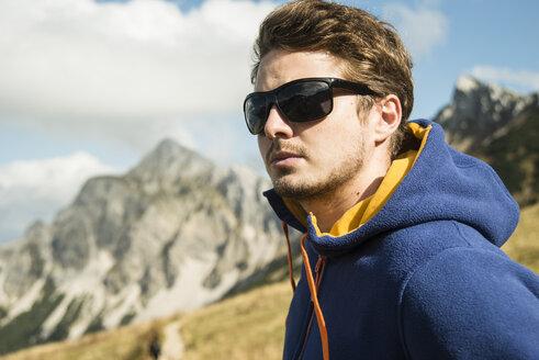 Austria, Tyrol, Tannheimer Tal, young man wearing sunglasses - UUF002252