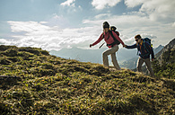 Austria, Tyrol, Tannheimer Tal, young couple hiking hand in hand on alpine meadow - UUF002257