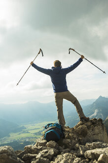 Austria, Tyrol, Tannheimer Tal, young man with hiking poles cheering on mountain top - UUF002283