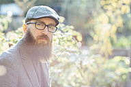 Portrait of beared man wearing glasses and a cap sitting in a garden - FX000072