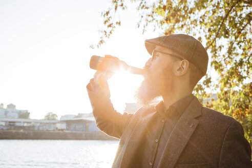 Beared man drinking beer out of a bottle at backlight - FX000081