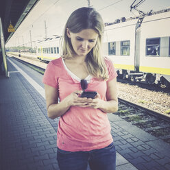 Woman with cell phone at train station - SAR000903
