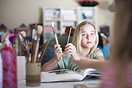 Girl in arts class holding brushes - ZEF001416
