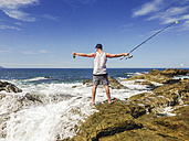 Young man with fishing pole standing at the pacific coast in Mexico, waves breaking on rocky shore. - ABAF001512
