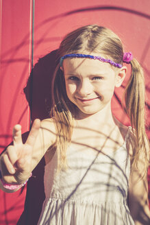 Portrait of smiling little girl in summer showing victory sign - SARF000923