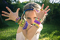 Portrait of little girl showing her loom bracelets - SARF000919