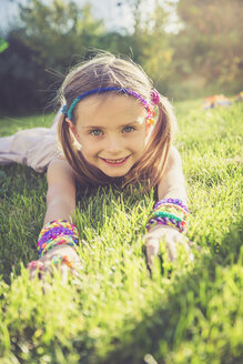 Portrait of smiling little girl with loom bracelets and hair-band lying on a meadow - SARF000915