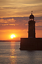 Germany, Bremen, Bremerhaven, Lighthouse on the pier at sunset - OLEF000041