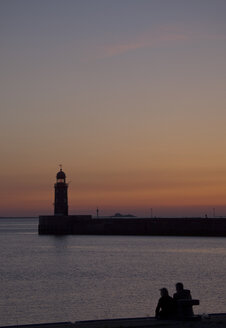 Germany, Bremen, Bremerhaven, Lighthouse on the pier at sunset - OLEF000039