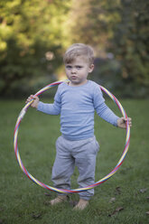 Portrait of serious looking little boy standing in the garden with hula-hoop - MW000080