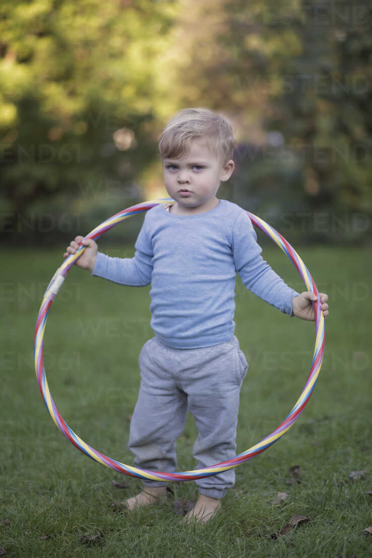 Portrait of serious looking little boy standing in the garden with hula-hoop - MW000080 - Martin Wimmer/Westend61