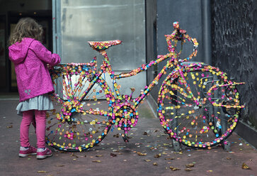 Austria, Linz, little girl looking at bicycle covered with colourful stickers - MW000081