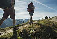 Austria, Tyrol, Tannheimer Tal, young couple hiking on mountain trail - UUF002204