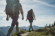 Austria, Tyrol, Tannheimer Tal, young couple hiking on mountain trail - UUF002201