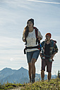 Austria, Tyrol, Tannheimer Tal, young couple hiking on mountain trail - UUF002200