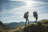 Austria, Tyrol, Tannheimer Tal, young couple hiking on mountain trail - UUF002198