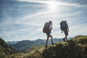 Austria, Tyrol, Tannheimer Tal, young couple hiking on mountain trail - UUF002198
