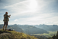 Austria, Tyrol, Tannheimer Tal, young man taking picture in mountainscape - UUF002194