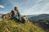 Austria, Tyrol, Tannheimer Tal, young couple having a rest in the mountains - UUF002193