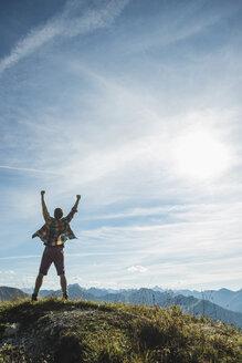 Austria, Tyrol, Tannheimer Tal, young man cheering on mountain top - UUF002183