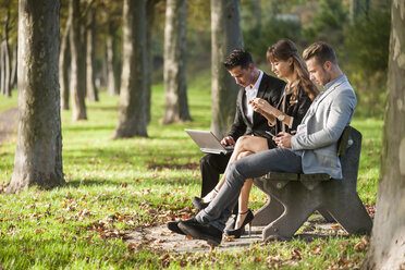 Three business people sitting on a park bench using laptop, smartphone and digital tablet - PAF001015