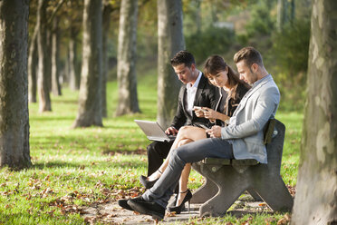 Three business people sitting on a park bench using laptop, smartphone and digital tablet - PAF001014